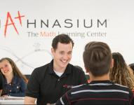 Mathnasium Smiling male instructor below Mathnasium wall sign